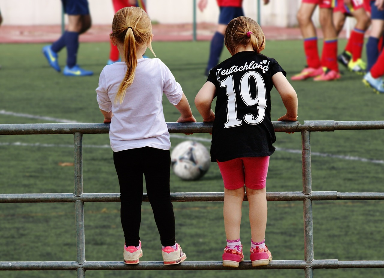 young soccer girls watching older girls play football ages 4-5