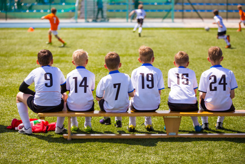 Age 7-9 youth soccer players sitting bench football kids