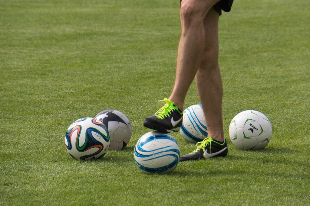 soccer balls and player trainer training kick a ball